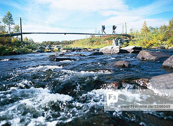 Zwei Männer auf eine Bergtour  überqueren eine Brücke  Schweden.