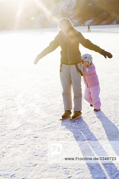 Mother and daughter skating against the light  Sweden.