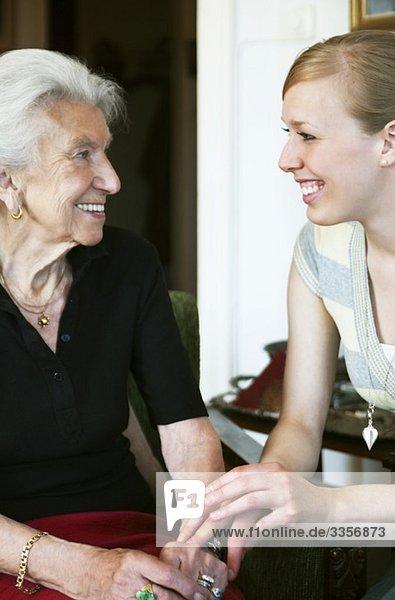 Frau  die sich um die ältere Dame kümmert.