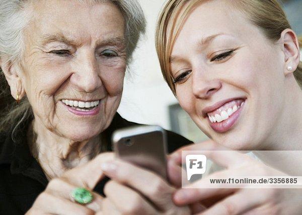 Zwei glückliche Frauen und ein Handy