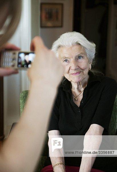 Junge Frau beim Fotografieren einer älteren Dame mit Fotohandy