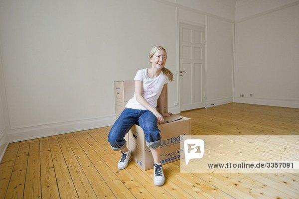 Woman sitting on moving box