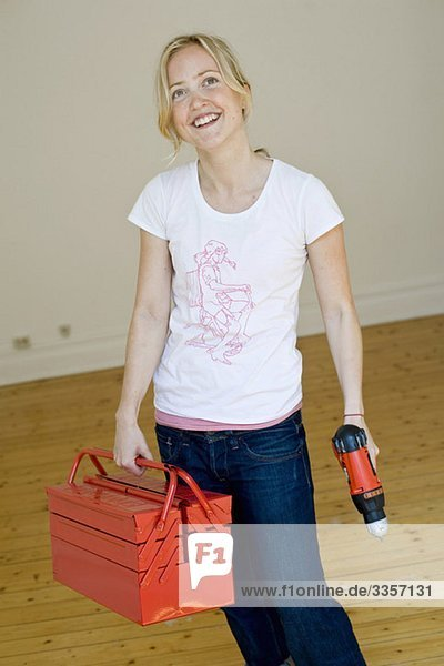 Frau im Raum stehend mit Werkzeugkasten und Schraubendreher