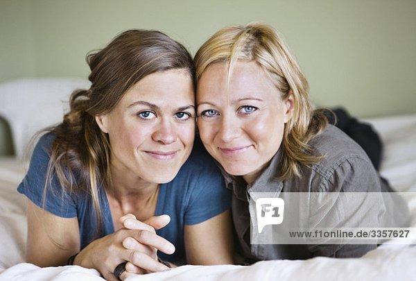 Lesbenpaar lächelt in die Kamera