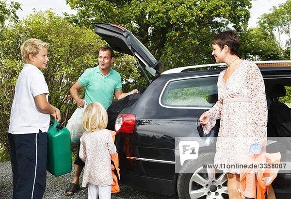 Große Familie beim Beladen des Autos