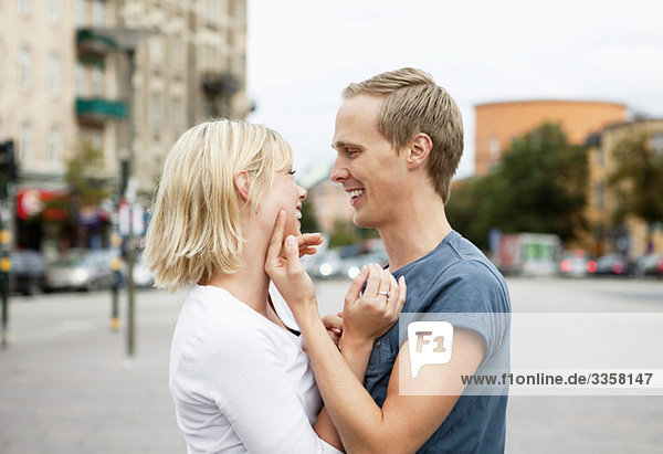 couple smiling to each other on street  side view
