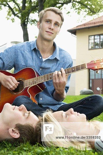 Ein Typ im Freien  der für seine Klassenkameraden Gitarre spielt.