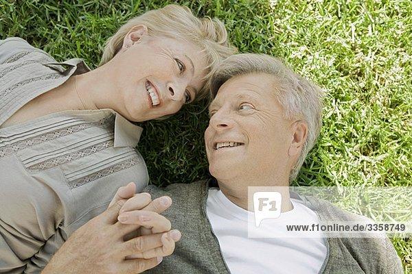Mann und Frau liegen Hand in Hand im Gras