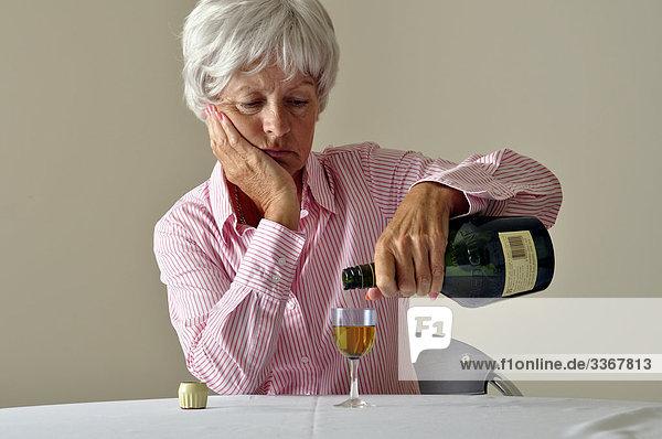 Interior  zu Hause  Senior  Senioren  Frau  Glas  Depression  Krankheit  Traurigkeit  1  reifer Erwachsene  reife Erwachsene  Alkohol  Einsamkeit  trinken  Flasche  Likör  alt  Sherry