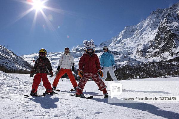 10873684  Switzerland  swiss  winter sports  winter chat  canton Valais  family  snow  winter  ski  skiing  Carving  Carvingski  mountains  alpine  Alps  sun  back light  plush cap  portrait  four  group  persons  children  Saas Fee