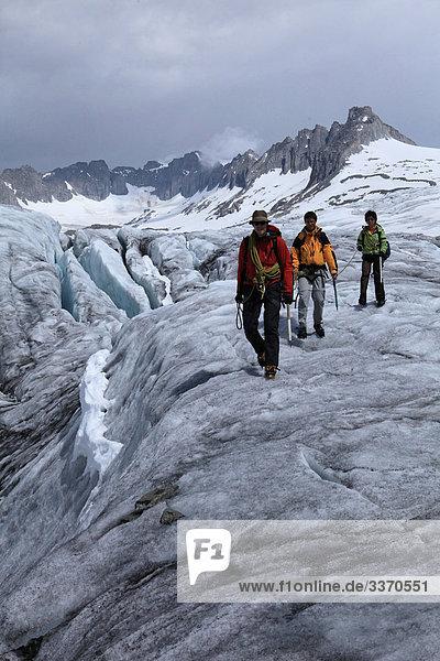 10873841  Switzerland  swiss  glacier tour  group  rope  three  Rhone glacier  walking  hiking  glacier  ice  moraine  canton Valais  weather  adventure  glacier fissure  persons  tour