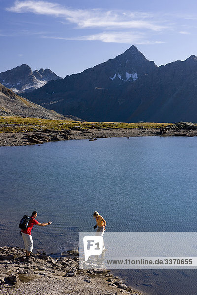 10874061  Switzerland  swiss  walk  hike  two  pair  couple  stones throw Graubunden  Grisons  Bundnerland  autumn  Fluelapass  persons  scenery  lake  black horn  mountains  nature  Davos  footpath  mountain lake  canton