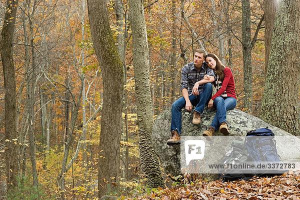 Junges Paar auf Felsbrocken im Wald sitzend