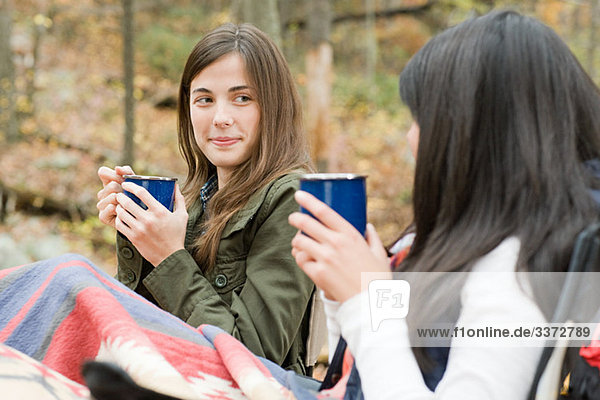 Junge Frauen beim Trinken auf dem Campingplatz