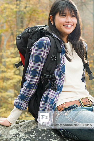 Young woman in forest with backpack