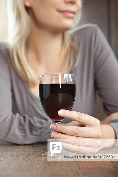 Junge Frau mit Rotwein in der Bar