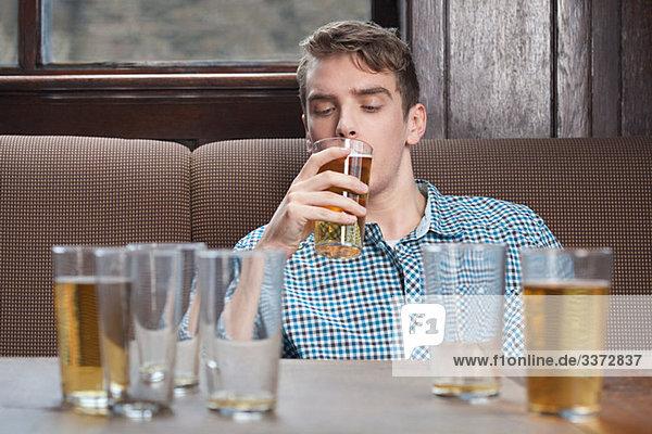 Junger Mann trinkt Bier in der Bar