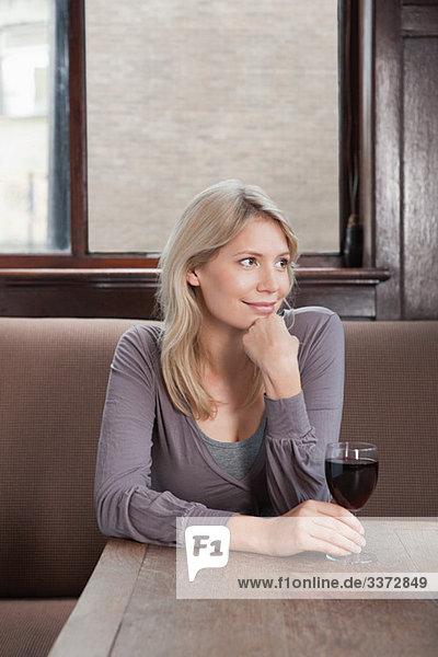Junge Frau in der Bar mit Rotwein