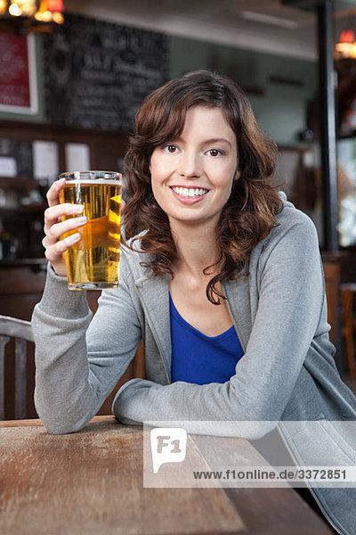 Junge Frau in der Bar mit einem Glas Bier