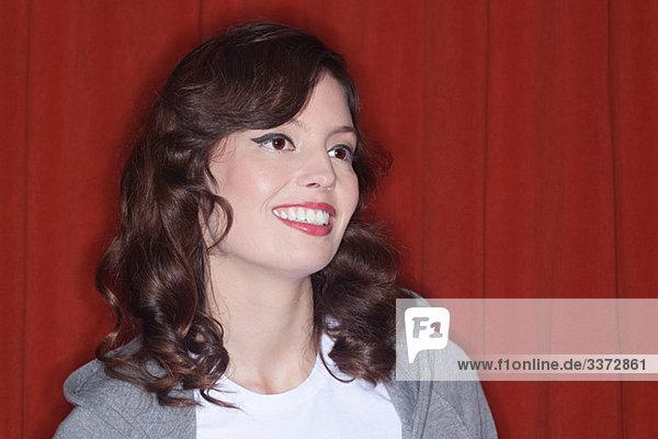 Porträt einer jungen Frau vor rotem Hintergrund