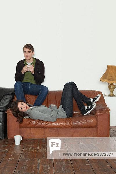 Junges Paar auf Ledersofa