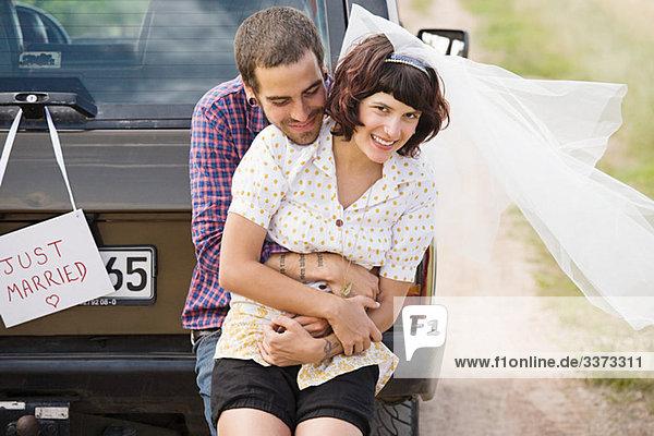 Neuvermähltes Paar mit dem Fahrzeug