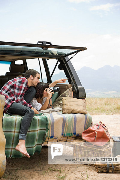 Paar im Heck des Geländewagens mit Fernglas