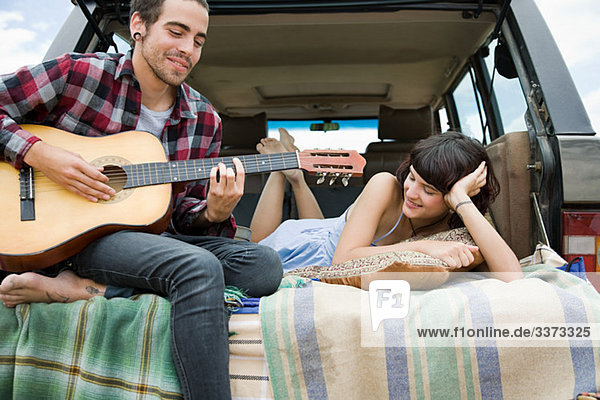 Junger Mann spielt Gitarre für Freundin