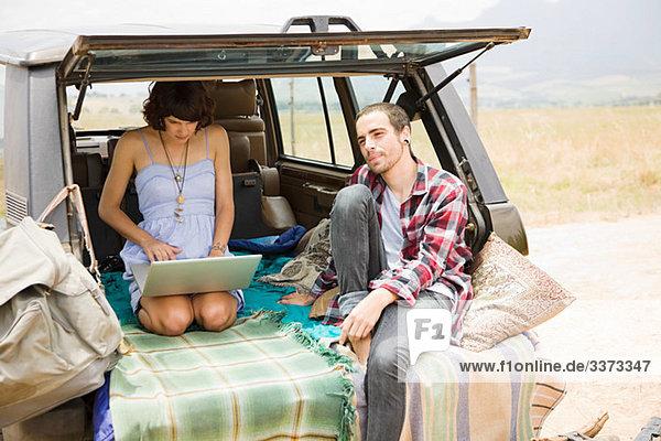 Paar im Geländewagen mit Laptop