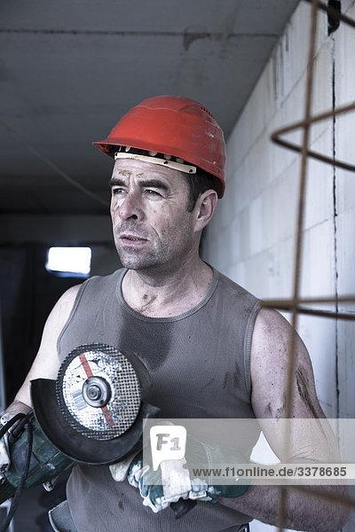 Bauarbeiter mit einer Werkzeugmaschine