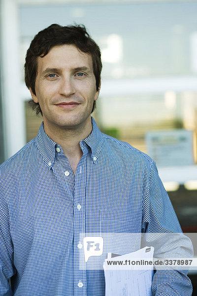 Mann mit Dokumenten unter dem Arm  Portrait