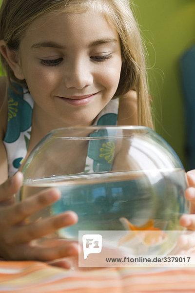 Mädchen beobachten Goldfische schwimmen im Fischglas
