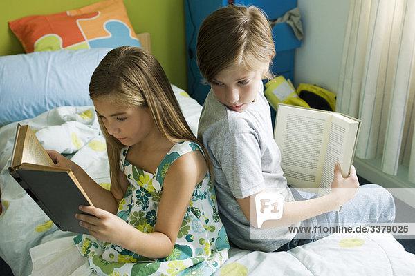 Siblings reading together  boy glancing over shoulder at sister's book