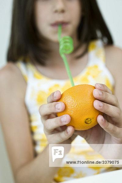 Mädchen trinkt Saft aus Orangenhälfte durch Stroh
