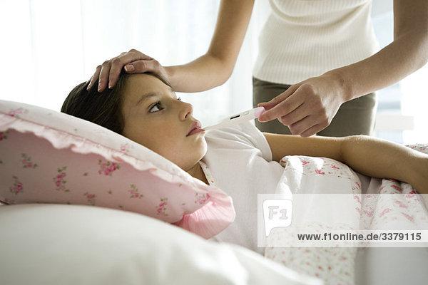 Mutter überprüft die Temperatur der Tochter  streichelt die Stirn