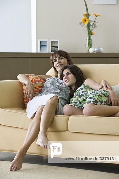 Mutter und Teenager-Tochter entspannen gemeinsam auf dem Sofa