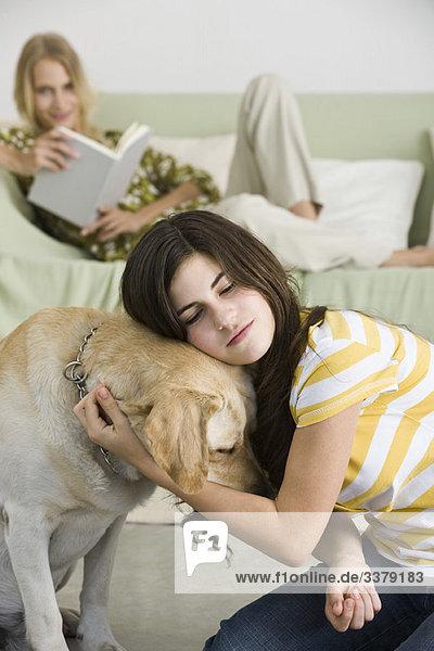 Teenager Mädchen umarmt Haustier Hund