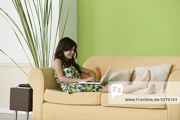 Teenager Mädchen entspannt auf dem Sofa mit Laptop im Wohnzimmer
