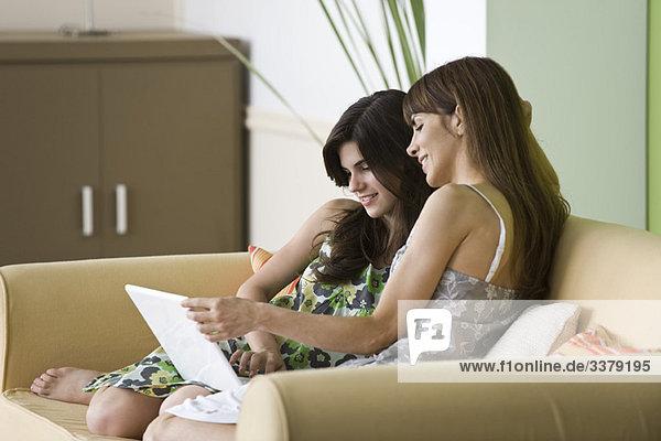 Mutter und Tochter im Teenageralter mit Laptop auf dem Sofa