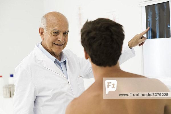 Arzt erklärt dem Patienten das Röntgenbild