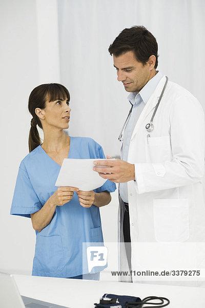 Krankenschwester zeigt Dokument dem Arzt