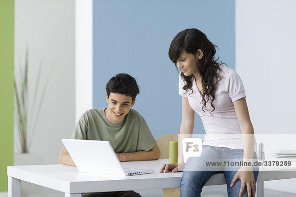 Teenager  die zusammen mit einem Laptop unterwegs sind.