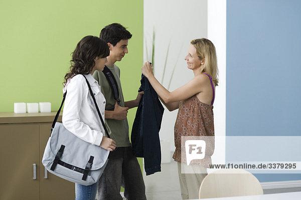 Teenager gehen aus  Mutter erinnert den Sohn daran  eine Jacke zu tragen.