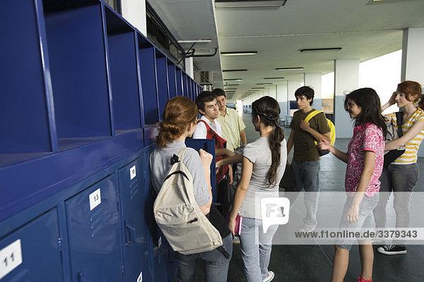 Gymnasiasten plaudern zusammen im Schulflur bei den Schließfächern