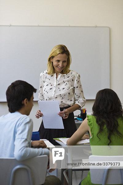 Lehrer spricht mit Schülern im Klassenzimmer