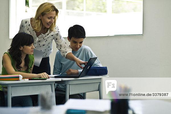Lehrer hilft Schülern bei der Nutzung von Laptops im Unterricht