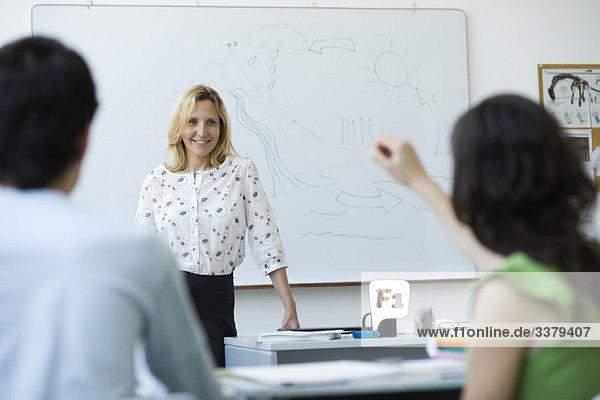Gymnasiallehrer steht vor der Klasse und beantwortet Frage