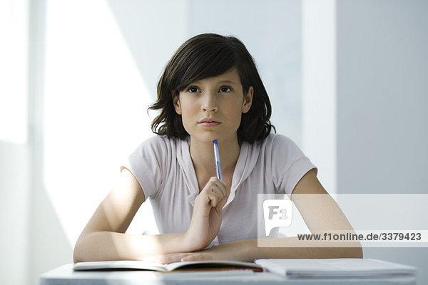 Teenager-Mädchen am Schreibtisch sitzend  nachdenkend  Porträt