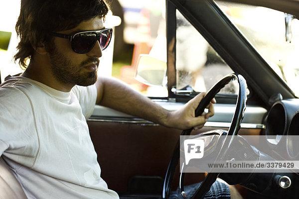 Macho junger Mann beim Fahren