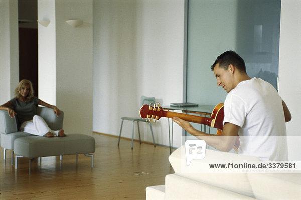 Mann spielt Akustikgitarre im Wohnzimmer  Frau schaut zu